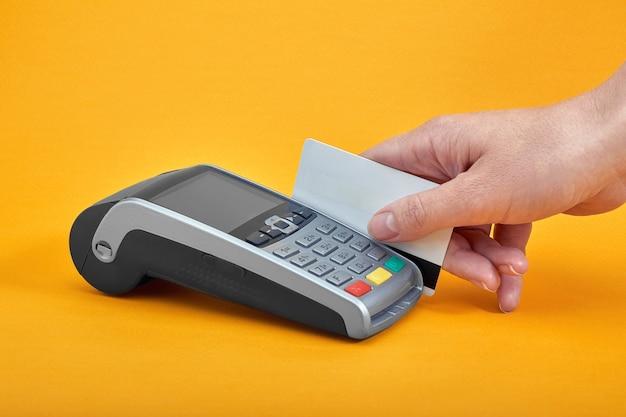 Крупный план кнопок платежного автомата с человеческой рукой, держащей пластиковую карту