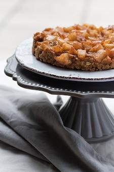 洋ナシとリンゴのクローズアップは、ケーキスタンドに崩れます。アーモンド小麦粉を使用したビーガングルテンフリーケーキ。