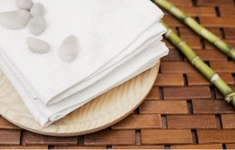 Close-up of pebbles; towel and bamboo plant on wooden tabletop