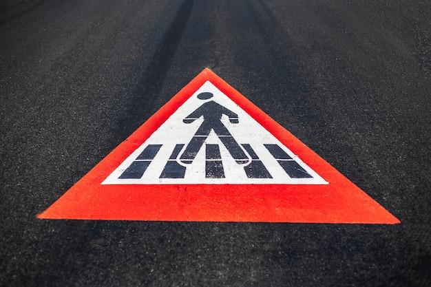 Крупный план пешеходного знака на асфальтированной дороге.
