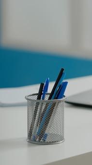 空のキャビネットの白い机の上のペンとラップトップのクローズアップ