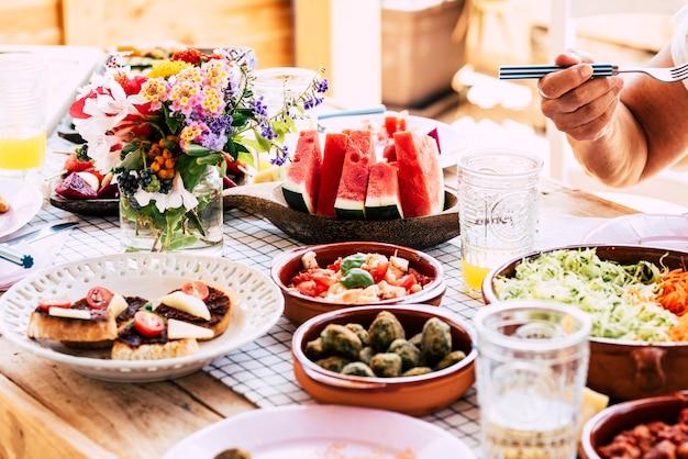 人々のクローズアップは、テーブルの上で健康的でベジタリアンまたはビーガンの食べ物を食べます