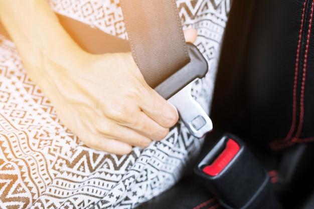 도로에서 운전하기 전에 안전을 위해 자동차에 안전 벨트를 고정하는 사람들의 닫습니다.