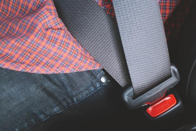 道路を運転する前に安全のために車のシートベルトを手で締める人のクローズアップ