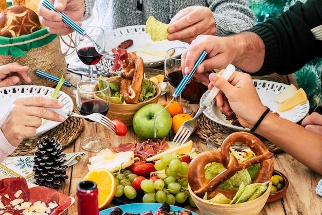 Закройте руки людей, собирающих еду с рождественского стола