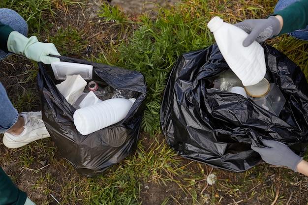地面からゴミを屋外のゴミ袋に入れる保護手袋をはめた人のクローズアップ