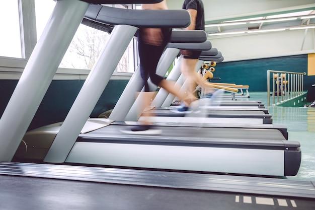 フィットネスセンターでのトレッドミルトレーニングセッション中に動いている人々の足のクローズアップ