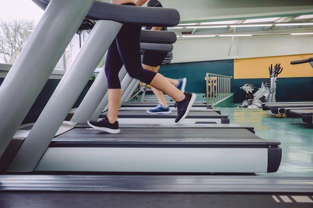 フィットネスセンターでのトレーニングセッションでトレッドミルの上を走っている人々の足のクローズアップ