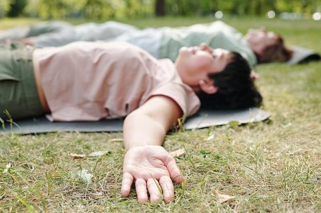 푸른 잔디에 누워 눈을 감고 휴식을 취하는 사람들의 클로즈업
