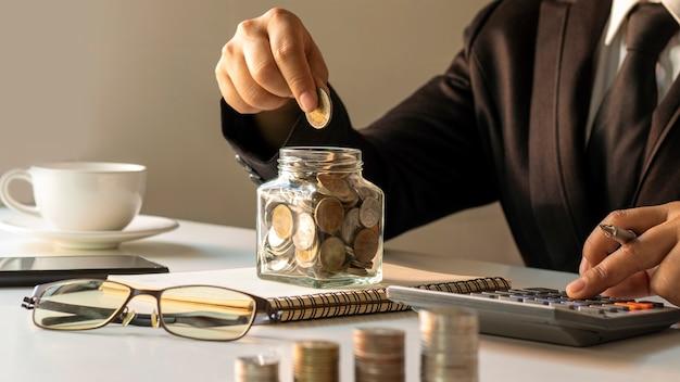 お金を節約するボトルや電卓にコインを入れてお金を節約し、銀行のアイデアを考えている人々のクローズアップ。