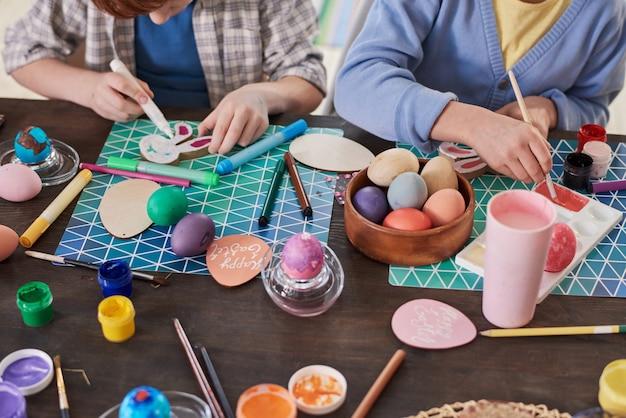 Крупный план людей, сидящих за столом и раскрашивающих яйца кистями, которые они вместе готовят к пасхе