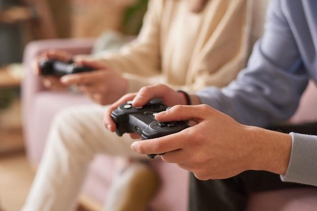 ジョイスティックでソファに座って、チームでビデオゲームをプレイしている人々のクローズアップ