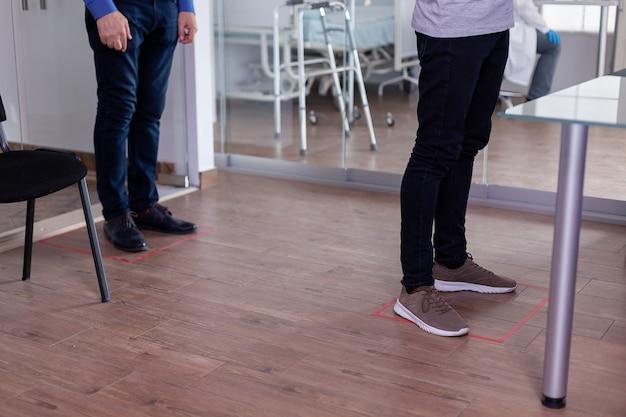 コロナウイルスに対する社会的距離を尊重する床の看板の待合室に立っている人々のクローズアップ