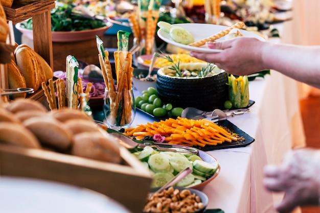 ケータリングセルフサービスでイベントパーティーでテーブルから食べ物を取る人々のクローズアップ