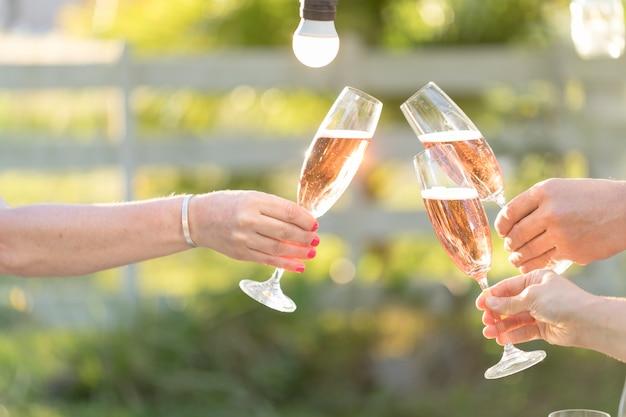 屋外でシャンパンで乾杯する人々のクローズアップ