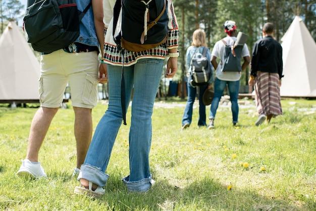 Крупный план людей с ранцами, стоящих на траве и выбирающих палатки в фестивальном лагере