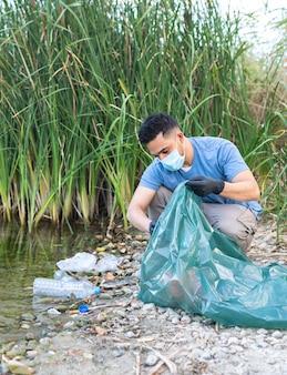 川からプラスチックを収集している人のクローズアップ。プラスチックの川を掃除する人。環境コンセプト。