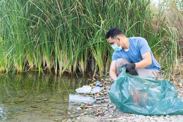 川からプラスチックを収集している人のクローズアップ。プラスチックの川を掃除する人。