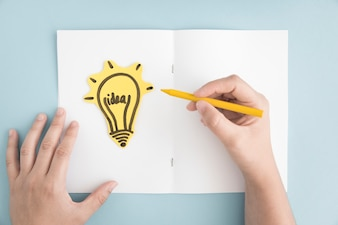 Close-up of person drawing light bulb on white page over the gray background