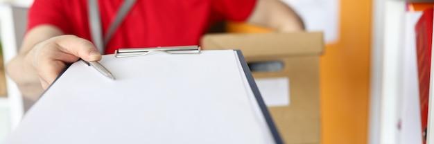 署名のためにクライアントにクリップボードを渡す人のクローズアップ。紙の上に敷設する銀のペン。概念