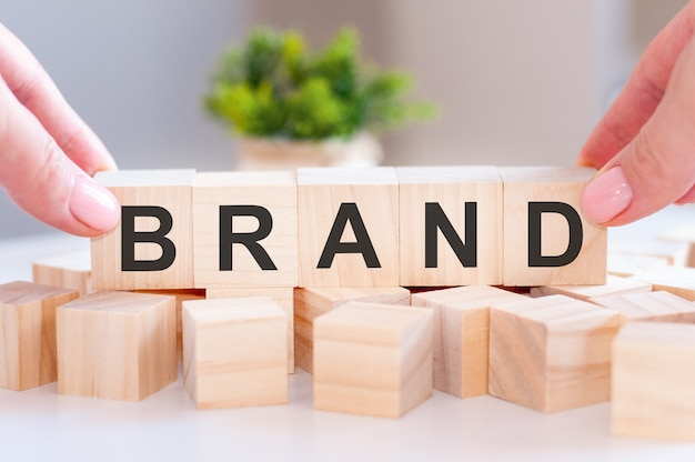 Крупный план человека, держащего слово бренд на деревянном столе