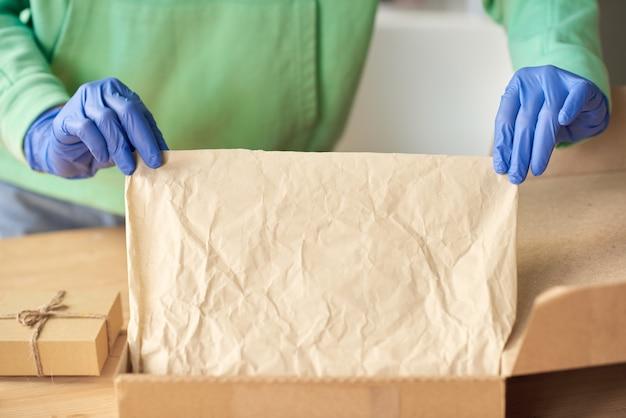 Крупный план человека в защитных перчатках, упаковывающего вещи в картонную коробку перед доставкой