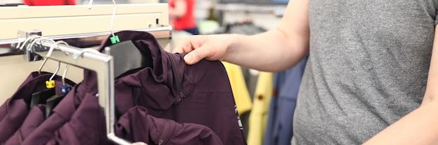 ショッピングセンターの人のクローズアップ。店でアウターを選ぶ男。スタンプのスタイリッシュで快適なジャケット。服にお金を使う大人。ワードローブ変更コンセプト