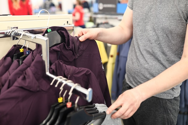 쇼핑 센터에있는 사람의 클로즈업입니다. 저장소에 겉옷을 선택하는 남자. 우표에 세련되고 편안한 재킷. 성인 옷에 돈을 지출합니다. 옷장 변경 개념