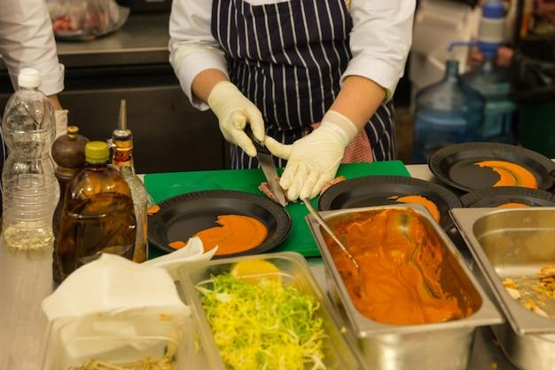 Крупным планом человека, готовящего отдельные тарелки на прилавке на кухне ресторана