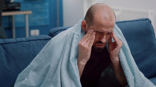頭痛に対してこめかみをこすっている人のクローズアップ