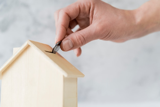 木造住宅piggybankにコインを挿入する人の手のクローズアップ