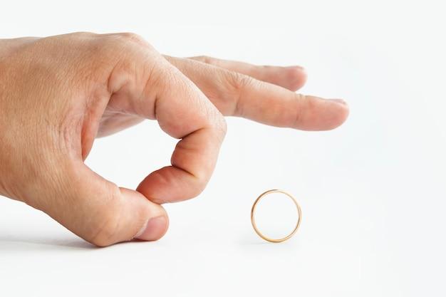 白で隔離の結婚式の金の指輪を押しのけて人の手のクローズアップ。男は指輪を指で蹴る。結婚したいという男性の不本意。結婚における幻滅。男性によって開始された離婚。