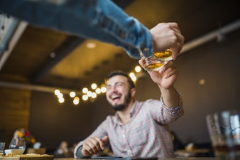 Close-up of person's hand toasting drinks with his friend