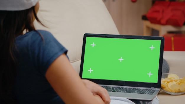 ノートパソコンで水平方向の緑色の画面を見ている人のクローズアップ