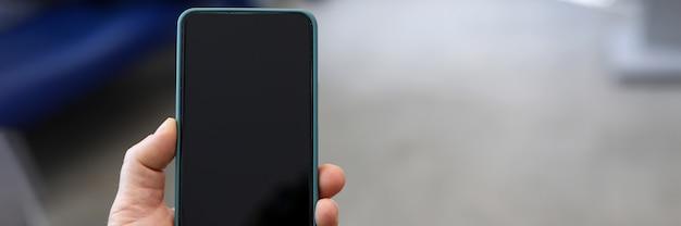 黒い画面で現代のスマートフォンを持っている人の手のクローズアップ。モックアップスタイル。右側にスペースをコピーします。楽しみや仕事のためのデバイス。テクノロジーとエンターテインメントのコンセプト