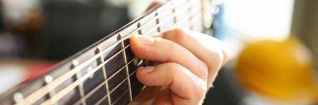 アコースティックギターで遊んでいる人の手のクローズアップ。楽器の美しいメロディーを実行する男性のマクロ撮影。魂の趣味。アーティストとミュージシャンのコンセプト