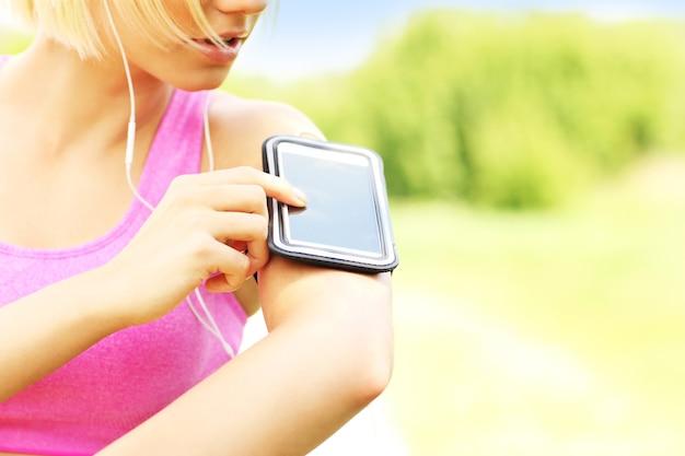 Крупный план телефона над подходящей бегущей женщиной в парке