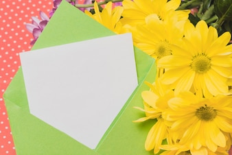 Close-up of piece of paper on envelope and yellow daisies