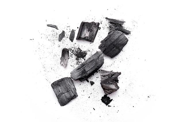부서진 나무 석탄, 재, 흰색으로 분리된 검은 가루 조각의 클로즈업. 평면도 프리미엄 사진