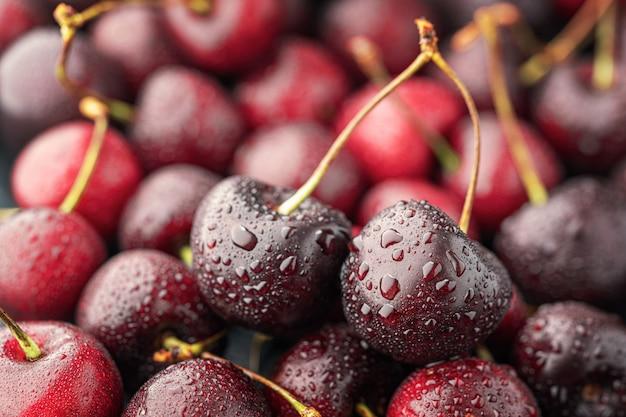 茎と熟したチェリーの山のクローズアップ。新鮮な赤いチェリーの大規模なコレクション。熟したチェリーの背景。