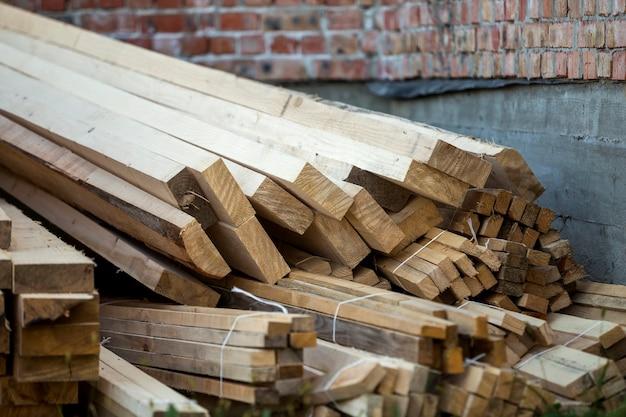 明るい太陽に照らされた自然な茶色の不均一な粗い木の板の積み重ねられたスタックのクローズアップ。大工、建築、修理、家具用の工業用木材、建設用の木材材料。