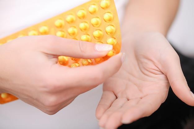 女性の手の丸薬のクローズアップ