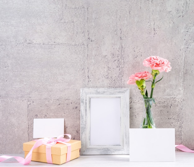 母の日の挨拶のための額縁と花瓶のピンクのカーネーションのクローズアップ