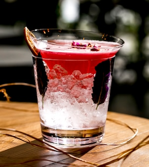 氷と暗いバジルの葉が付いているガラスに置かれたピンクのカクテルのクローズアップ