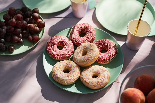 誕生日パーティーのコピースペースのために屋外で装飾された夏のピクニックテーブルのピンクのドーナツのクローズアップ