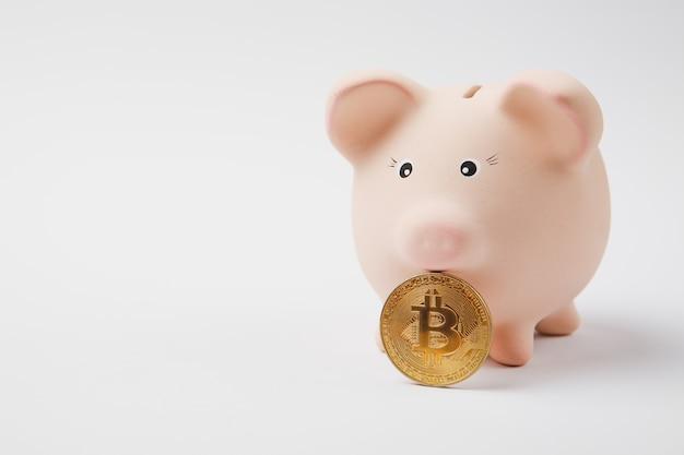 분홍색 돼지 저금통, 흰 벽 배경에 격리된 비트코인 미래 통화를 닫습니다. 돈 축적 투자 은행 또는 비즈니스 서비스 부의 개념. 공간 광고를 조롱하십시오.