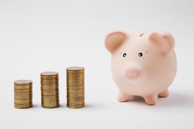 분홍색 돼지 저금통을 닫고 흰 벽 배경에 격리된 금화 더미를 닫습니다. 돈 축적 투자 은행 또는 비즈니스 서비스, 부 개념. 공간 광고를 조롱하십시오.