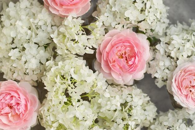 방울과 물과 핑크 장미 꽃과 흰색 수국 닫습니다
