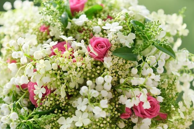 ピンクのバラの花と滴と谷の白いユリのクローズアップ