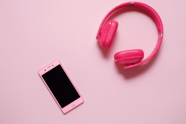 분홍색 배경에 분홍색 헤드폰 핑크 스마트 폰의 클로즈업. (평면도). 음악 듣기